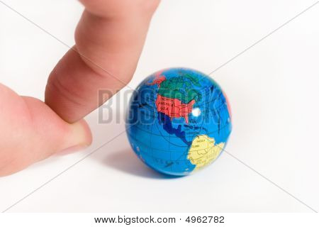 Human Fingers Ready To Push A Small Globe