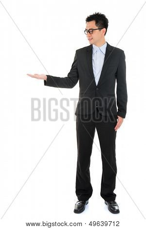 Full body portrait of young handsome smiling Asian business man hand showing blank empty space, standing isolated over white background