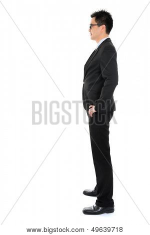 Side view full body Asian business man in formal suit standing isolated on white background
