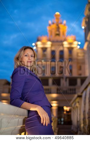 Beautiful girl is leaning on the parapet in the evening city