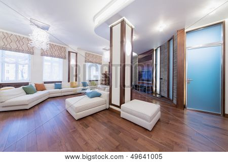 The spacious, well lit living room with a round glass table, chairs and sofa