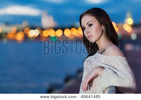 A young woman is standing on the waterfront leaning on railing against the background of night city