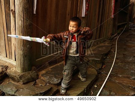 Chinese Five Year Old Boy Playing With A Plastic Sword In The Village Street, Editorial Images.