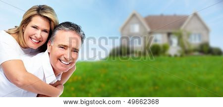 Happy senior couple near new house. Real estate background.