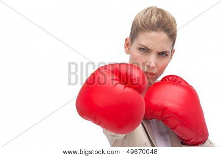 Businesswoman wearing boxing gloves on white background