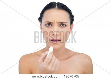Frowning natural model using chap stick on white background