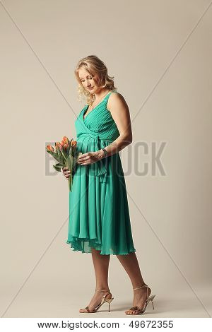 Happy Young Pregnant Woman Holding Flowers