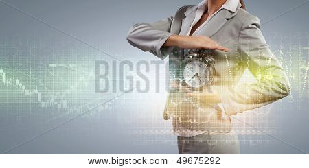 Image of businesswoman holding alarmclock against illustration background
