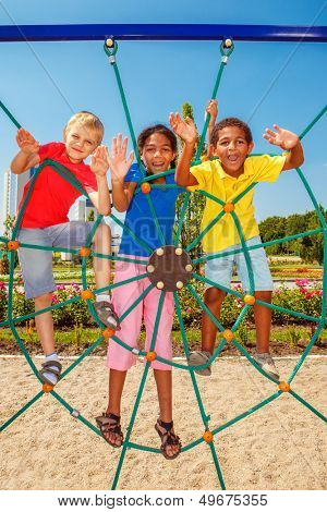 Cheerful friends climbing the net at a city playground
