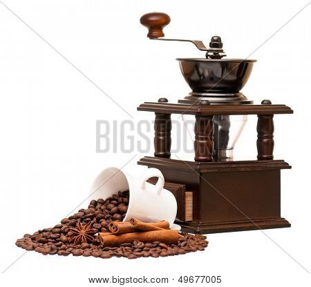 Manual coffee grinder with coffee beans and cup, isolated on white background