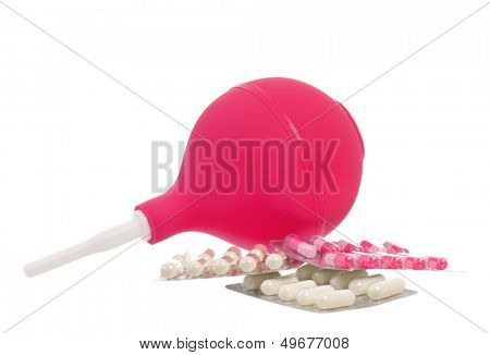 Medical pink enema and colorful pills, isolated on white background