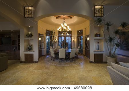 Lit chandelier over circular dining room of a spacious and modern home