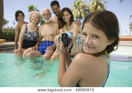 Portrait of smiling girl with video camera recording family in swimming pool