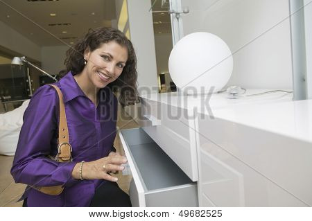 Portrait of happy middle aged woman examining dresser in furniture store