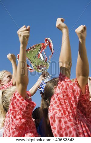 Low angle side view of happy girls soccer team with trophy against clear blue sky