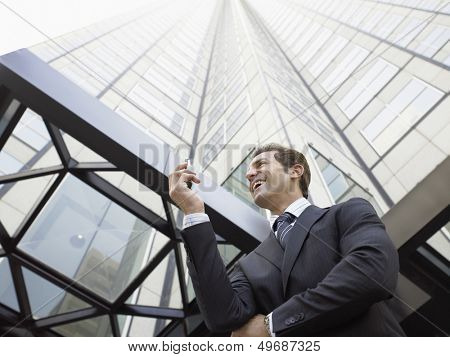 Low angle view of businessman reading SMS on mobile phone against office building