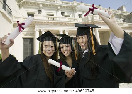 Portrait of beautiful young students with diplomas standing in front of university