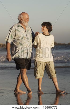 Full length of happy grandfather and grandson walking on beach at dusk