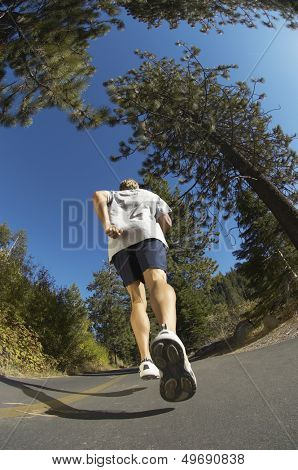 Low angle view of young man jogging on road
