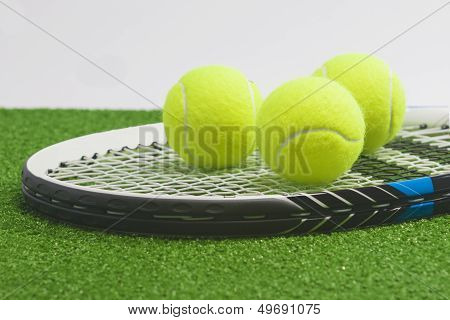 Tennis Concept: Closeup, Tennis Racket With Balls Lies On Green Grass Court