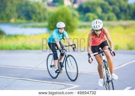 Training Cycle  Of The Two Female Caucasian Sportswomen Riding Sport Bikes Outdoors