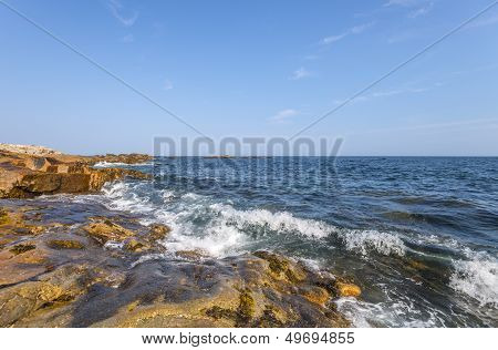 Ocean Waves Crashing Against A Rocky Shore