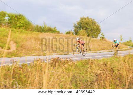 Training Process Of Two Female Caucasian Sportswomen Riding Bikes Outdoors