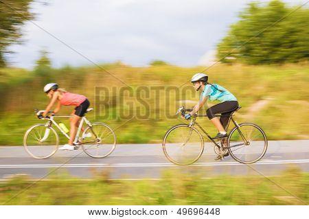 Training Process Of Two Female Caucasian Sportswomen Riding Sport Bikes Outdoors