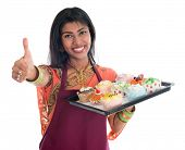 stock photo of sari  - Happy Traditional Indian woman in sari baking bread and cupcakes and showing thumb up - JPG
