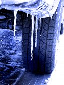 stock photo of icy road  - Snowy winter road with tire tracks in snow and tire and icicles - JPG