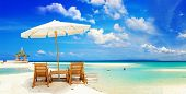 View of nice tropical empty sandy beach with umbrella and beach chair