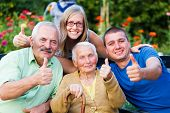 stock photo of grandmother  - Happy contented family showing thumbsup for the quality of the residential care of grandmother - JPG