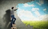 stock photo of wall cloud  - Young man drawing a cloudy blue sky on the wall - JPG