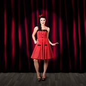 stock photo of rockabilly  - Dancing woman wearing retro rockabilly dress performing on a theatre stage in a depiction of cabaret beauty and glamour - JPG
