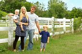 image of morals  - a happy attractive family of four people a mother father baby and young child are standing outside by a white picket fence on a summer day - JPG