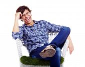 stock photo of legs crossed  - Young man in checkered shirt and blue jeans sitting in white chair with hand near his head and laughing - JPG