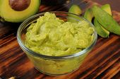 stock photo of dipping  - Fresh guacamole dip in a glass bowl with fresh avocado - JPG