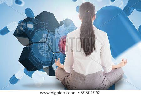 Businesswoman sitting in lotus pose against blue pills floating