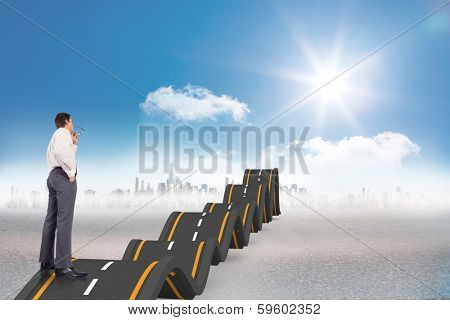 Thinking businessman holding glasses against bumpy road leading to city