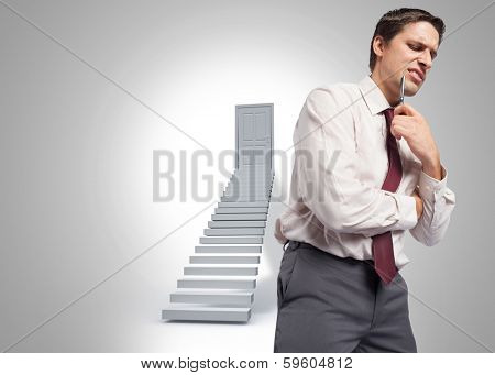 Thoughtful businessman holding pen to chin against shut door at top of steps