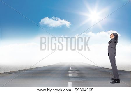 Thinking businessman scratching head against open road