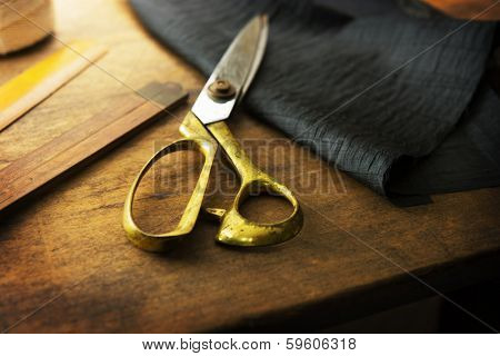 Measuring and cutting textile or fine cloth. Work table of a tailor. Gold scissors and black fabric.