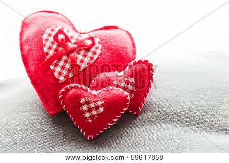 Handmade plush red hearts on the soft pillow. Romantic love, Valentine's Day concepts.