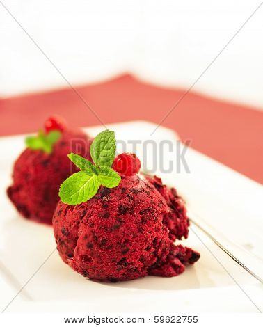 Ice-cream globule with a currant and mint on a red napkin