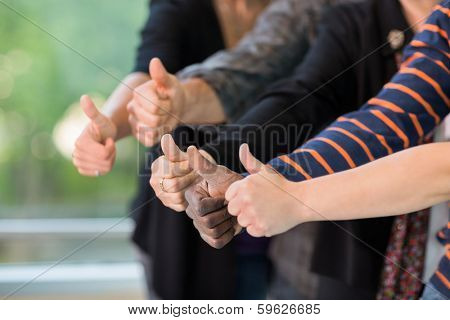 Cropped image of multiethnic university students gesturing thumbsup together