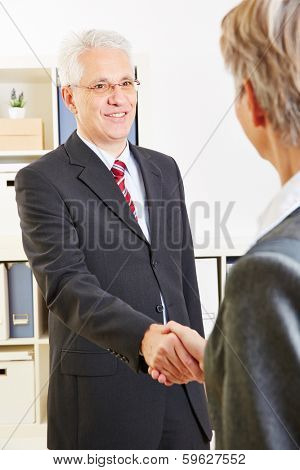 Two business people greeting at team meeting in office