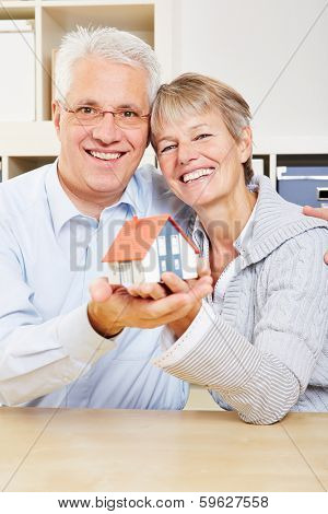 Happy senior couple holding a small house in their hands