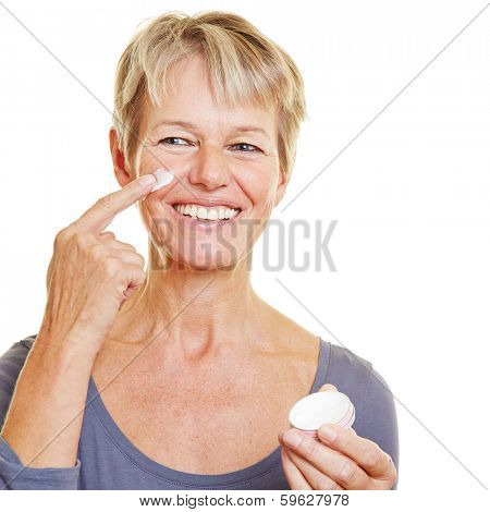 Smiling elderly woman putting skin care lotion on her face