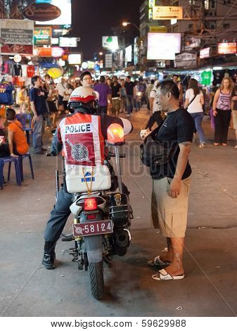 BANGKOK, THAILAND - JANUARY 9, 2012: Local man talks on the street with policeman on the motorcycle on Khao San Road. Royal Thai Police counts about 230,000 officers.