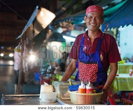 BANGKOK, THAILAND - JANUARY 9, 2012: Local man stands behind his street food stall and smiles to the camera. Everyday thousands of tourists and locals buys food on these stalls.